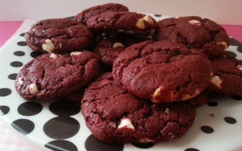 Red velvet white chocolate chip cookies on a polka dot plate. New cookbook recipes.